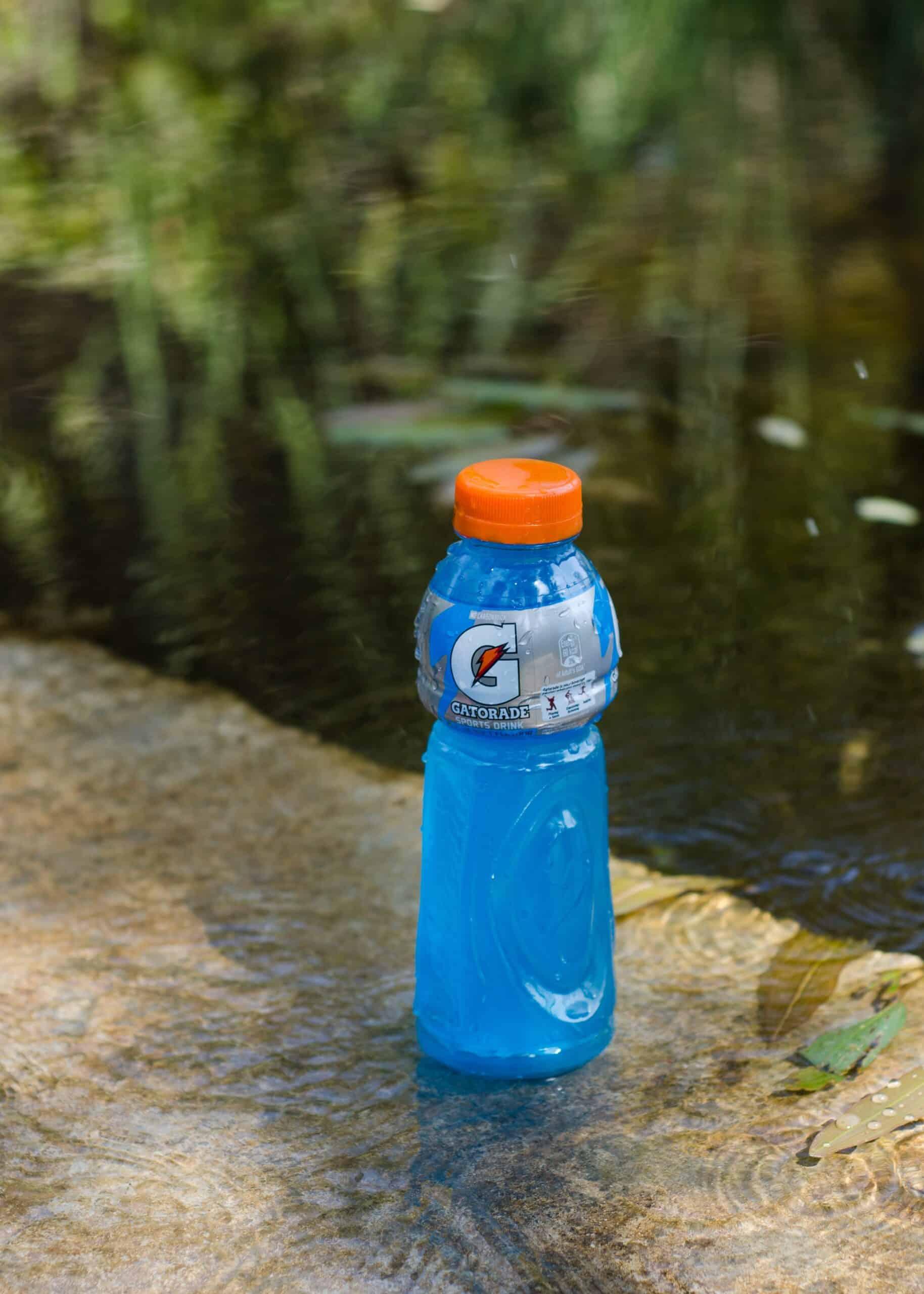 bottle of gatorade next to a pond